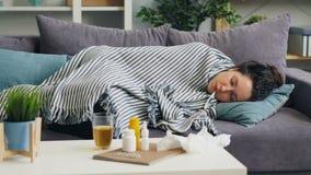 Estudiante enfermo que toma una siesta con el termómetro en la boca que miente en el sofá debajo de la manta almacen de video