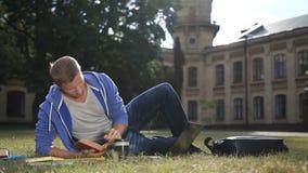 Estudiante enfocado hermoso que estudia en césped del campus almacen de metraje de vídeo
