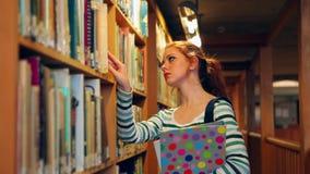 Estudiante enfocado que escoge un libro en la biblioteca metrajes
