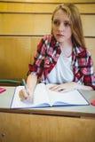 Estudiante enfocado que toma notas durante clase Imagen de archivo libre de regalías