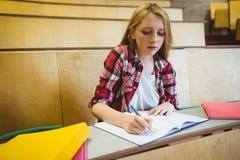 Estudiante enfocado que toma notas durante clase Fotografía de archivo libre de regalías