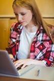Estudiante enfocado que usa el ordenador portátil durante clase Fotografía de archivo