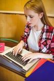 Estudiante enfocado que usa el ordenador portátil durante clase Imagen de archivo libre de regalías