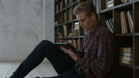 Estudiante enfocado que usa la tableta en biblioteca almacen de metraje de vídeo