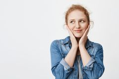 Estudiante europeo del pelirrojo feliz blando que lleva a cabo las manos en mejillas como si siendo avergonzado o tocado, mirando Imagen de archivo libre de regalías
