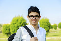 Estudiante feliz con el bolso, al aire libre Foto de archivo libre de regalías