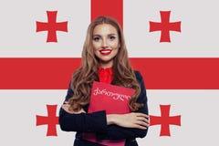 Estudiante feliz con el libro rojo contra el fondo de la bandera de Georgia Aprenda y viaje concepto fotografía de archivo libre de regalías