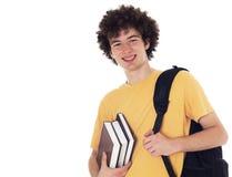 Estudiante feliz con la mochila y los libros. Fotografía de archivo