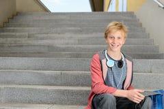 Estudiante feliz con la tableta que se sienta en pasos Fotografía de archivo