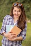 Estudiante feliz con los apoyos que sostienen los libros afuera Imagen de archivo libre de regalías