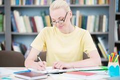 Estudiante feliz con los vidrios que escribe en biblioteca Foto de archivo