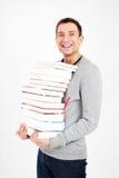 Estudiante feliz con una pila de libros Foto de archivo libre de regalías