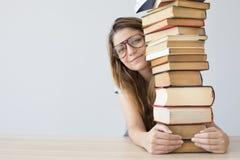 Estudiante feliz con una pila de libros Imagen de archivo