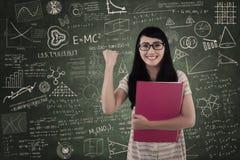 Estudiante feliz en clase en tablero escrito Foto de archivo