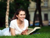 Estudiante feliz en parque de la ciudad con un libro Foto de archivo libre de regalías