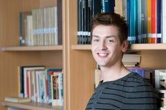 Estudiante feliz en una biblioteca Imágenes de archivo libres de regalías