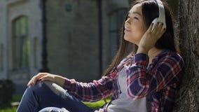 Estudiante feliz hermoso que disfruta de música preferida que eso suena en sus auriculares metrajes