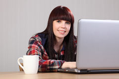 Estudiante feliz hermoso que hace la preparación en la computadora portátil Foto de archivo libre de regalías