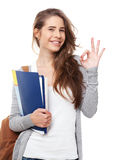 Estudiante feliz joven que muestra la muestra aceptable aislada en blanco Foto de archivo