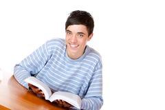 Estudiante feliz joven que se sienta en el libro de lectura del escritorio Foto de archivo libre de regalías