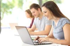 Estudiante feliz que busca en línea en la sala de clase Foto de archivo