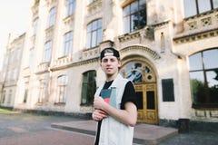 Estudiante feliz que camina en campus en su universidad Un individuo en un casquillo y una chaqueta del dril de algodón en la ent Foto de archivo