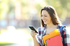 Estudiante feliz que camina y que usa un teléfono móvil Imágenes de archivo libres de regalías
