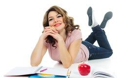 Estudiante feliz que estudia en el piso aislado en blanco Imagen de archivo libre de regalías