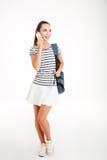 Estudiante feliz que habla en el teléfono y que mira lejos Imágenes de archivo libres de regalías