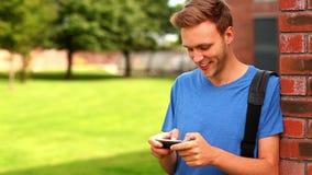 Estudiante feliz que manda un SMS en su teléfono afuera almacen de metraje de vídeo