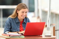 Estudiante feliz que mecanografía en un ordenador portátil en una barra Imagen de archivo libre de regalías