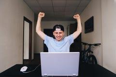 Estudiante feliz que mira un ordenador portátil y que disfruta mientras que aumenta sus manos para arriba Sitio adolescente Foto de archivo
