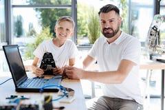 Estudiante feliz que se sienta cerca de su profesor de la robótica Imagen de archivo libre de regalías