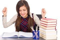 Estudiante feliz que se sienta en el escritorio, manos en el aire Fotos de archivo