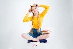 Estudiante feliz que se sienta en el piso con el libro Fotos de archivo