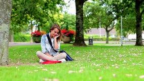 Estudiante feliz que se sienta en la hierba que hace una llamada de teléfono metrajes