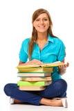 Estudiante feliz que se sienta en un suelo con una pila de libros Imágenes de archivo libres de regalías