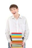 Estudiante feliz que sostiene la pila de los libros Fotografía de archivo