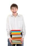 Estudiante feliz que sostiene la pila de los libros Imagen de archivo libre de regalías