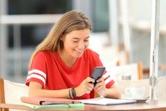 Estudiante feliz que usa un teléfono elegante en un restaurante Imagen de archivo