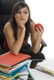 Estudiante femenino al estudiar con la manzana Imágenes de archivo libres de regalías