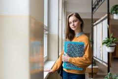 Estudiante femenino atractivo joven de la High School secundaria que hace una pausa la ventana en el vestíbulo en su escuela Fotografía de archivo libre de regalías