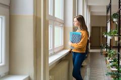 Estudiante femenino atractivo joven de la High School secundaria que hace una pausa la ventana en el vestíbulo en su escuela Imagenes de archivo