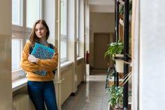 Estudiante femenino atractivo joven de la High School secundaria que hace una pausa la ventana en el vestíbulo en su escuela Fotografía de archivo