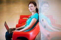 Estudiante femenino bastante joven con la computadora portátil Imagen de archivo libre de regalías