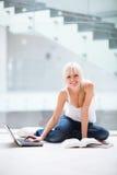 Estudiante femenino bonito con la computadora portátil y los libros Imagen de archivo