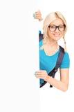 Estudiante femenino bonito que presenta detrás del panel blanco Fotos de archivo libres de regalías