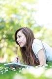Estudiante femenino con el libro de trabajo al aire libre Fotos de archivo libres de regalías