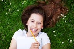 Estudiante femenino con el libro de trabajo al aire libre Fotografía de archivo libre de regalías