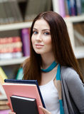 Estudiante femenino con los libros en la biblioteca Fotos de archivo